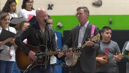 Isaac Slade, left, and Gov. John Hickenlooper, right, on Monday (credit: CBS)